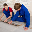 Young handsome men laid laminate floor covering, perform repairs — Stock Photo #48583745