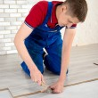 Young handsome men laid laminate floor covering, perform repairs — Stock Photo #48583761