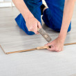 Young handsome men laid laminate floor covering, perform repairs — Stock Photo #48583769