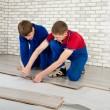 Young handsome men laid laminate floor covering, perform repairs — Stock Photo #48583779