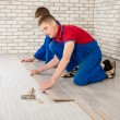 Young handsome men laid laminate floor covering, perform repairs — Stock Photo #48583781