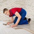 Young handsome men laid laminate floor covering, perform repairs — Stock Photo #48583797