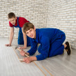 Young handsome men laid laminate floor covering, perform repairs — Stock Photo #48583807