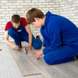 Young handsome men laid laminate floor covering, perform repairs — Stock Photo #48583835
