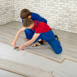 Young handsome men laid laminate floor covering, perform repairs — Stock Photo #48583977