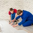 Young handsome men laid laminate floor covering, perform repairs — Stock Photo #48583993