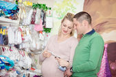 беременная женщина, покупая детскую одежду в супермаркете. молодая беременная женщина, выбирая новорожденных одежда — Стоковое фото