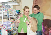 Pregnant woman buying baby clothes in supermarket .  Young pregnant woman choosing newborn clothes — Stock Photo