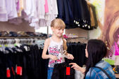 Cute beautiful little girl with her mother to buy clothes in sho — Stock Photo