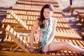 Young beautiful girl lying on a chaise lounge on the beach — Stock Photo