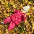 A small girl is lying on yellow leaves — Stock Video