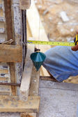 Labor man using a plumb bob for check — Stock Photo