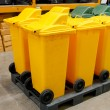 Foto de Stock  : Row of large yellow wheelie bins for rubbish