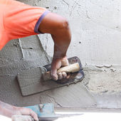 Plasterer concrete worker at wall of house construction — Stock Photo