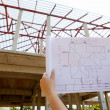 Architecture drawings in hand on house building — Stock Photo #38137401