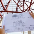 Architecture drawings in hand on house building — Stock Photo #38137491