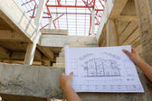 Architecture drawings in hand on house building — Stock Photo
