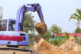 Backhoe tractor works on a construction site — Stock Photo