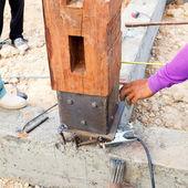Labor man using a plumb bob for check pillar — Stock Photo