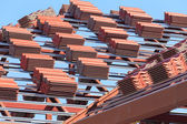 Roof under construction with stacks of roof tiles for home build — Stok fotoğraf