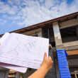 Architecture drawings in hand on big house building  — Stock Photo #45477427