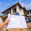 Architecture drawings in hand on big house building — Stock Photo #45477463