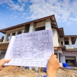 Architecture drawings in hand on big house building — Stock Photo #45477475