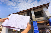 Architecture drawings in hand on big house building  — Stock Photo