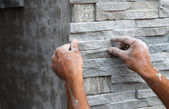Worker install stone wall surface with cement for house — 图库照片