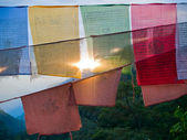 Setting sun shining through colorful prayer flags with the himal — Stock Photo