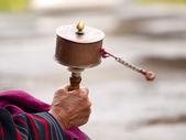 An older women spinning her prayer wheel — Stock Photo