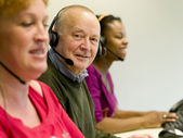 Telemarketing employees with headsets on — Stock Photo