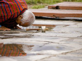 An older man praying to Buddha with a prayer wheel in front of him on the ground — Stock Photo