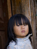 Young poor Bhutanese girl standing in front of her shed — Stock Photo