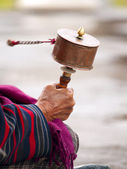 An older women spinning her prayer wheel — Stock Photo