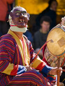 A masked man making music during a Bhutanese tsechus — Stock Photo
