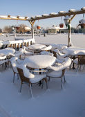 Snow covered furniture of a bar in the winter — Stock Photo