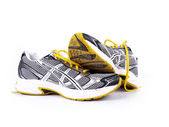 Used dirty pair of running shoes over a white background — 图库照片