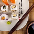 Fresh sushi and sashimi on a plate with chopsticks and soy sauce — Stock Photo