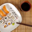 Fresh sushi and sashimi on a plate with chopsticks and soy sauce — Stock Photo #36079049