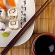 Fresh sushi and sashimi on a plate with chopsticks and soy sauce — Foto Stock
