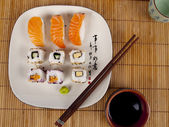 Fresh sushi and sashimi on a plate with chopsticks — Stock Photo