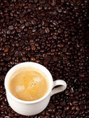 Fresh cup of dark roasted coffee with coffeebeans — Stock Photo