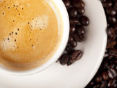 Top view of a cup of dark roasted coffee with coffeebeans — Stock Photo