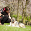 Beautiful girl petting her dog during a walk in the spring — Stock Photo