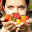 Beautiful girl smelling fresh strawberries in the spring — Stock Photo #44805361