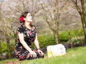 Beautiful girl enjoying the sun during a picnic in the spring — Stock Photo