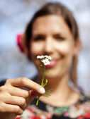 Beautiful girl handing over a cuckoo flower in the spring — Stock Photo
