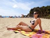 Beautiful girl in bikini tanning on the beach in the summer — Stock Photo