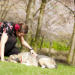 Beautiful girl petting her dog during a walk in the spring — Stock Photo #45704601
